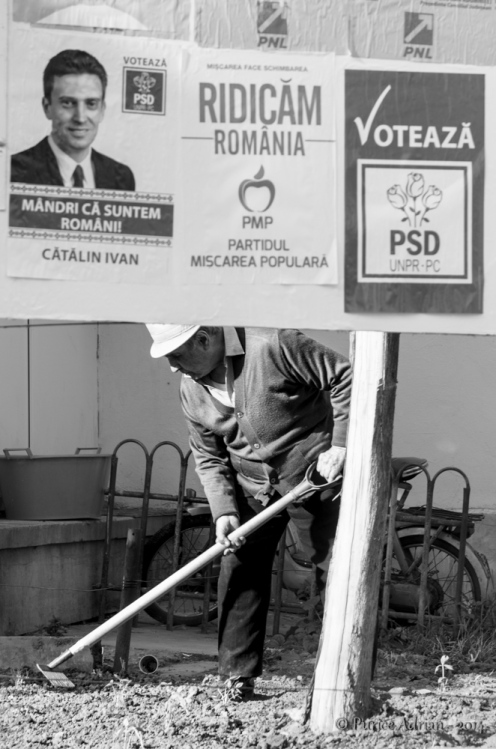 old guy working the land near election posters