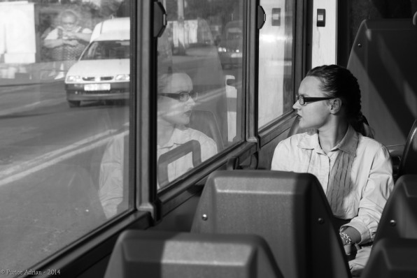 girl's reflection on a bus window