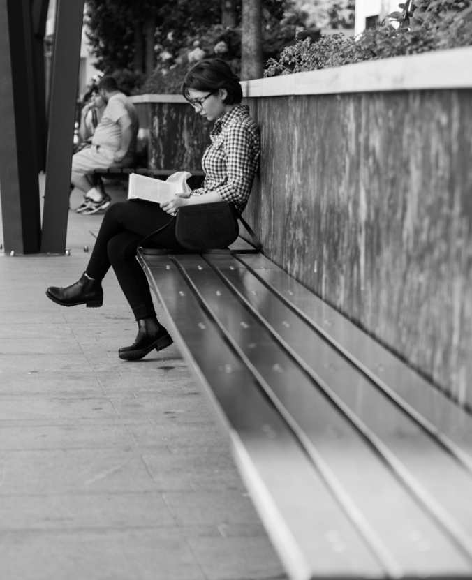 young girl reading a book on a bench