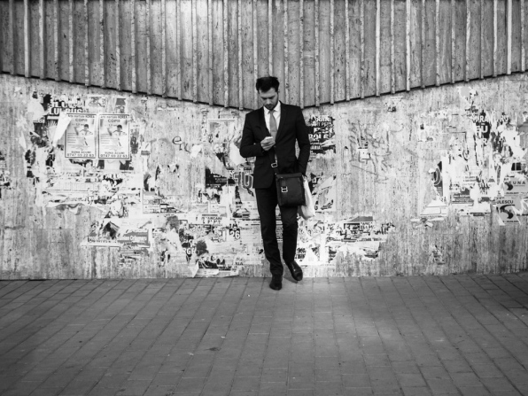 man in suit leaning against a wall