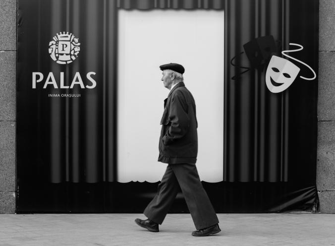 old guy walking in front of a scene
